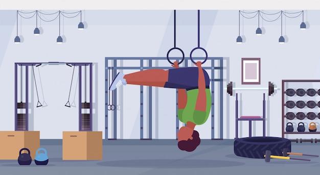 Uomo sportivo facendo anello dips esercizi con anelli di ginnastica ragazzo afroamericano allenamento cardio crossfit allenamento concetto moderno palestra centro benessere interno studio orizzontale a figura intera