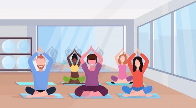 Gente sportiva che si siede la posa del loto che fa le esercitazioni di yoga che mescolano le donne degli uomini della corsa che risolvono orizzontale integrale interno della palestra moderna di concetto di stile di vita sano di forma fisica