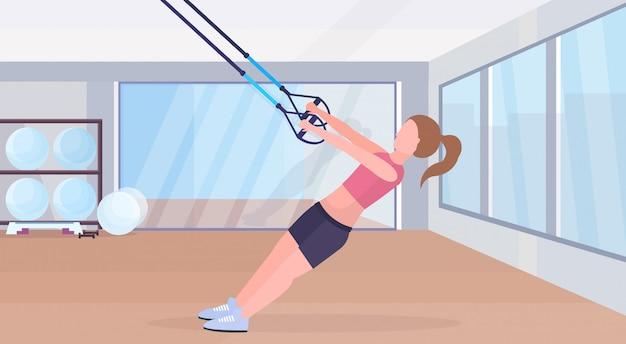 Donna sportiva che fa le esercitazioni con le cinghie di forma fisica della sospensione cinghie elastiche ragazza allenamento crossfit concetto di allenamento palestra moderna studio interno orizzontale piano integrale