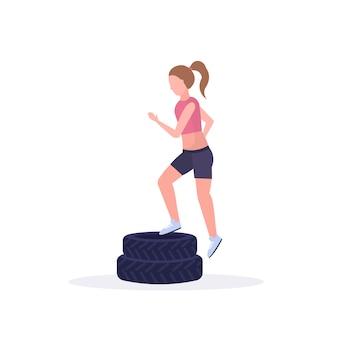Donna sportiva che fa gli edifici occupati sull'addestramento della ragazza della piattaforma delle gomme nel fondo sano di bianco di concetto del crossfit di stile di vita di allenamento delle gambe della palestra
