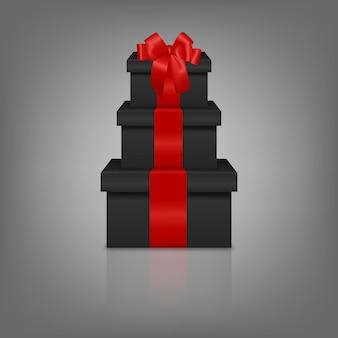 Pila di tre scatole regalo nere realistiche con nastro rosso e fiocco