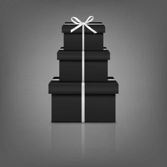 Pila di tre scatole regalo nere realistiche con nastro bianco e fiocco