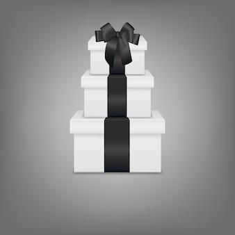 Pila di tre scatole regalo bianche realistiche con nastro nero e fiocco Vettore Premium