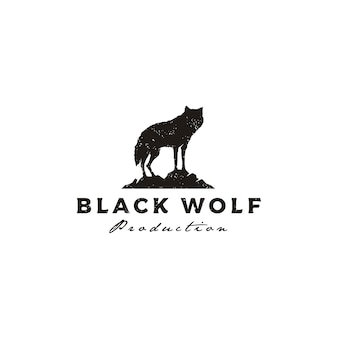In piedi lupo nero cane fox coyote jackal sulla roccia vintage rustico silhouette retrò hipster logo design