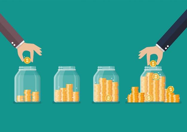 Passo della mano risparmio di monete in vaso di vetro
