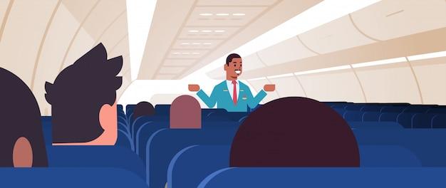 Steward che spiega le istruzioni per i passeggeri assistente di volo maschio afroamericano in uniforme che mostra le uscite di emergenza concetto di dimostrazione di sicurezza orizzontale dell'aeromobile bordo interno