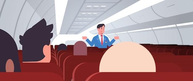 Steward spiegando le istruzioni per il passeggero maschio assistente di volo in uniforme che mostra le uscite di emergenza concetto di dimostrazione di sicurezza a bordo dell'aereo orizzontale orizzontale