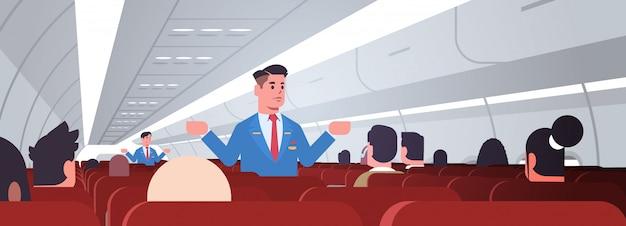 Steward spiegando le istruzioni per i passeggeri assistenti di volo di sesso maschile in uniforme che mostra le uscite di emergenza concetto di dimostrazione di sicurezza interno dell'aeroplano