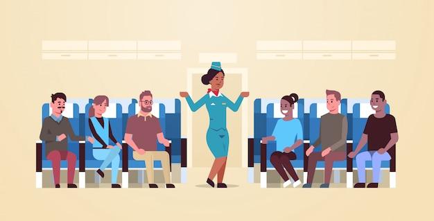 Hostess che spiega le istruzioni per i passeggeri della corsa mix afroamericano assistente di volo in uniforme che mostra le uscite di emergenza concetto di dimostrazione di sicurezza aereo bordo interno orizzontale