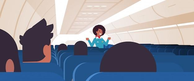 Hostess che spiega le istruzioni per i passeggeri assistente di volo afroamericano in uniforme che mostra le uscite di emergenza concetto di dimostrazione di sicurezza orizzontale aereo bordo interno