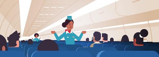 Hostess che spiega le istruzioni per i passeggeri assistenti di volo afroamericani in uniforme che mostra le uscite di emergenza concetto di dimostrazione di sicurezza orizzontale dell'aeroplano bordo interno