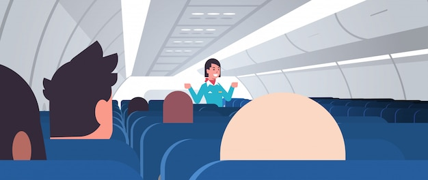 Hostess che spiega le istruzioni per i passeggeri assistente di volo femminile in uniforme che mostra le uscite di emergenza concetto di dimostrazione di sicurezza interni a bordo dell'aeroplano