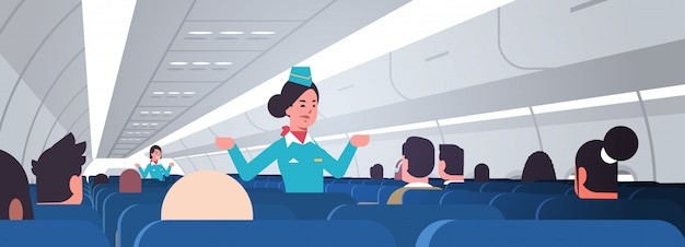Hostess che spiega le istruzioni per i passeggeri assistenti di volo femminili in uniforme che mostra le uscite di emergenza concetto di dimostrazione di sicurezza interno dell'aeroplano