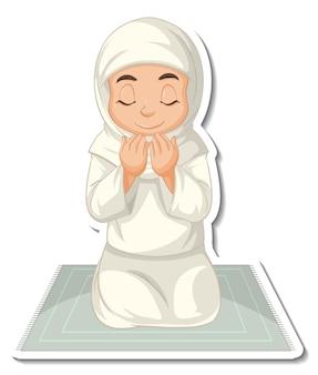 Un modello di adesivo con una ragazza musulmana seduta sul tappeto e che prega