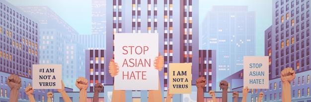 Ferma l'odio asiatico. mani umane che tengono manifesti contro il razzismo. supporto durante la pandemia di coronavirus covid-19