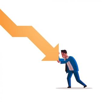 Uomo d'affari sollecitato che ferma freccia economica che cade concetto di rischio di investimento di fallimento di crisi finanziaria integrale