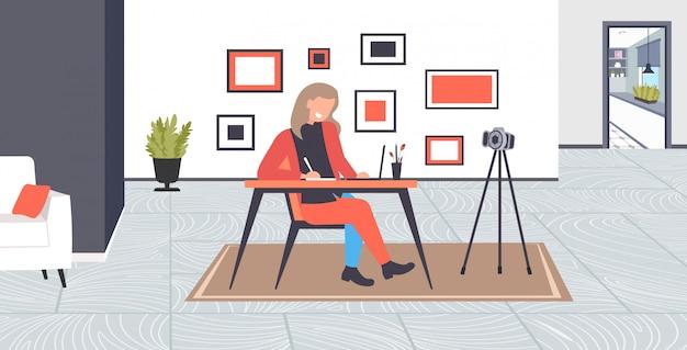 Studente blogger usando il portatile facendo i compiti di registrazione video online con fotocamera su treppiede blogging streaming live studiando concetto interno soggiorno a figura intera