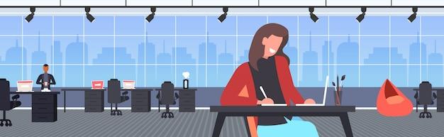 Blogger dello studente che per mezzo del computer portatile che fa il compito che registra video online con la macchina fotografica sul blogging del treppiede in streaming in diretta studiando il ritratto orizzontale interno dell'ufficio di concetto