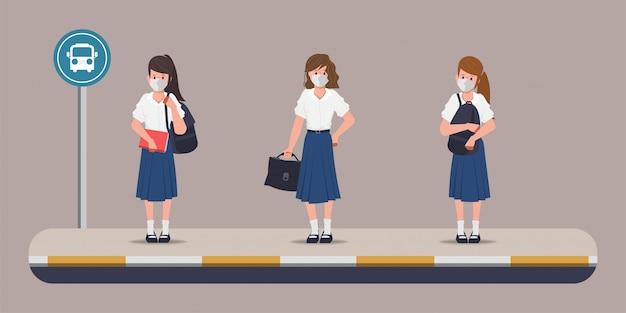 Studente alla fermata dell'autobus per tornare a scuola con un nuovo concetto normale.