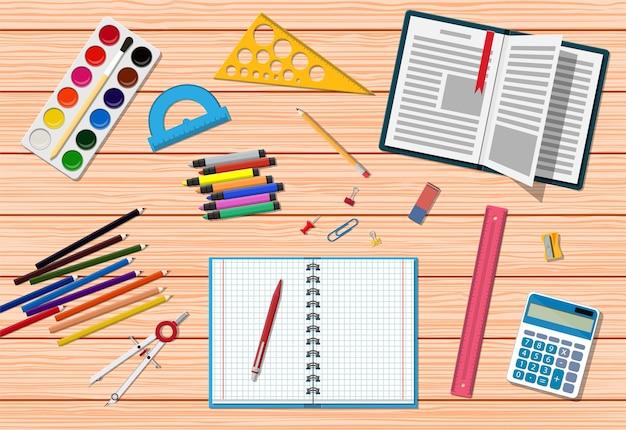 Scrivania in legno per studenti. articoli per l'istruzione scolastica o universitaria, elementi di studio ed educativi. nota righello matita penna libro calcolatrice vernice gomma temperamatite. di nuovo a scuola. stile piatto illustrazione