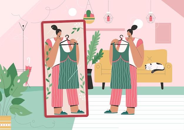 La ragazza alla moda sceglie il nuovo vestito in piedi davanti allo specchio
