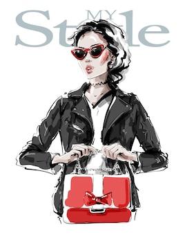 Ragazza alla moda in occhiali da sole che tengono borsa