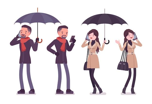 Uomo e donna alla moda con l'ombrello e il telefono nell'illustrazione dei vestiti di autunno
