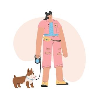 La donna alla moda sta con il cane al guinzaglio.