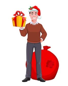 Uomo d'affari di successo in cappello della santa e con regali
