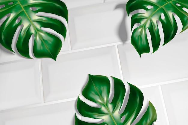 Sfondo estate con foglie tropicali su piastrelle bianche