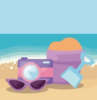 Scena della spiaggia di estate con la macchina fotografica e il secchio della sabbia