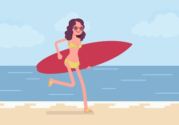 Ragazza del surfista su una spiaggia