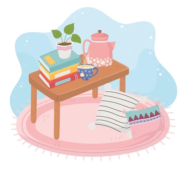 Tavola domestica dolce con la pila di bollitore della tazza di tè della pianta in vaso dei libri