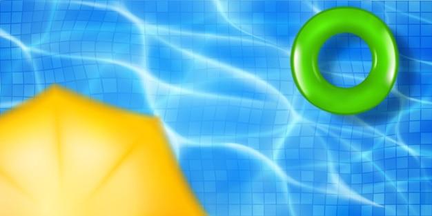 Vista dall'alto della piscina con tessere di mosaico, anello gonfiabile e tenda da sole. superficie dell'acqua in colori blu chiaro con riflessi di luce solare e increspature caustiche. priorità bassa di vacanza estiva.