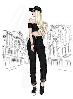 Una ragazza alta e snella con i capelli lunghi in pantaloni, top e berretto. modello alla moda.