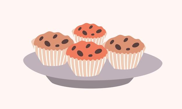 Gustosi cupcakes dolce con gocce di cioccolato che si trovano sulla piastra isolata su bianco. delizioso dessert, pasticceria o pasticceria al forno
