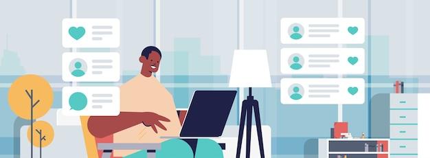 Blogger tecnologia registrazione video blog online live streaming blogging concetto uomo afroamericano vlogger utilizzando laptop soggiorno interno ritratto orizzontale