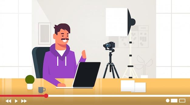 Tecnologia blogger registrazione video online uomo test nuovo laptop blogging concetto vlogger spiegando dispositivo digitale dispositivo funzionale seduto sul posto di lavoro orizzontale ritratto