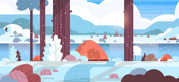 Area di campeggio tende nella foresta invernale concetto di paesaggio innevato natura con acqua montagne e colline