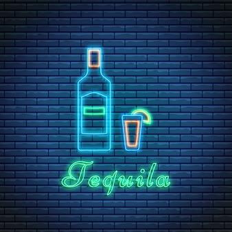 Bottiglia e vetro di tequila con iscrizione nello stile al neon sul fondo del mattone. cocktail bar simbolo, logo, cartello.