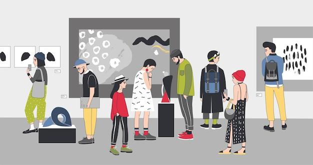 Visitatori premurosi della galleria d'arte contemporanea che guardano le mostre.