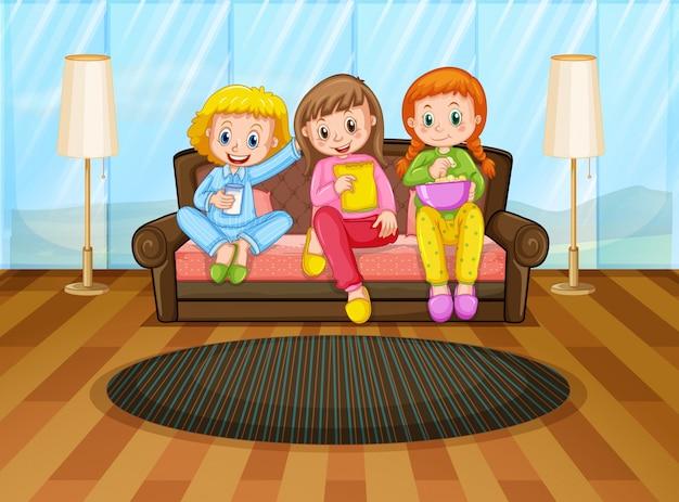 Tre ragazze che mangiano spuntini nel salotto