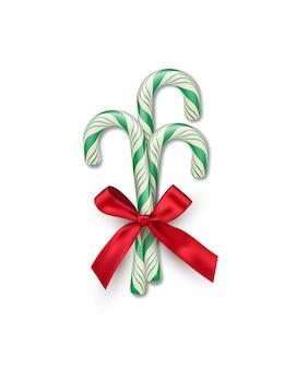 Tre bastoncini di zucchero a strisce verdi con fiocco rosso isolato su sfondo bianco elemento di design natalizio