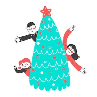 Tre bambini felici che salutano da dietro un albero di natale