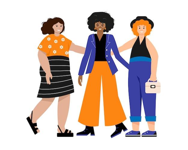 Tre donne o ragazze felici vestite con abiti alla moda in piedi insieme