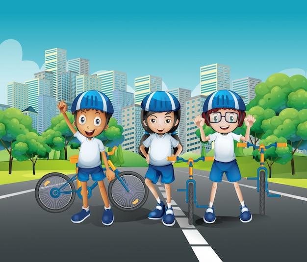 Tre bambini in sella alla bici sulla strada