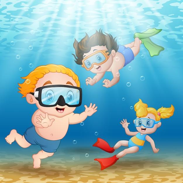 Tre bambini che nuotano e si tuffano sott'acqua