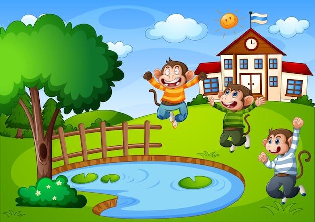 Tre scimmiette nella scena della natura con edificio scolastico
