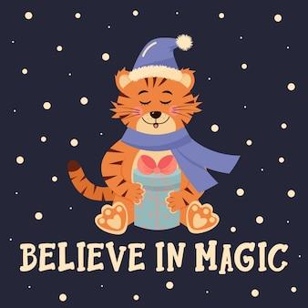 La tigre con il cappello e la sciarpa di babbo natale è seduta con un regalo credi nelle lettere magiche
