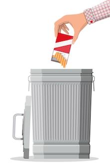 Concetto di abuso di tabacco. mano che mette il pacchetto di sigarette nel cestino. vietato fumare. rifiuto, proposta di fumo ..
